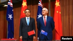 Australia's Prime Minister Malcolm Turnbull stands with Chinese Premier Li Keqiang before the start of an official signing ceremony at Parliament House in Canberra, Australia, March 24, 2017.