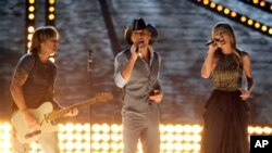 Dari kiri ke kanan: Penyanyi Keith Urban, Tim McGraw dan Taylor Swift tampil pada malam penganugerahan Academy of Country Music Awards (ACMA) ke-48 di Las Vegas (7/4). (Foto: Chris Pizzello/Invision/AP)
