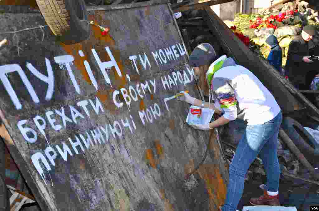 "The girl is painting a slogan that reads ""Putin you can kill us but you can't take away our freedom"" in Kyiv's Independence Square, Ukraine, Mar. 8, 2014. (Jamie Dettmer/VOA)"