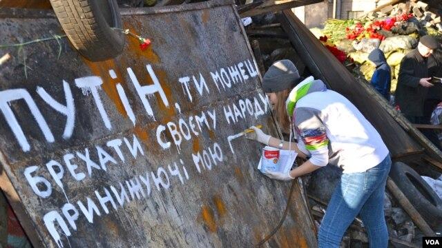 """Một cô gái sơn hàng chữ """"Putin ông có thể giết chúng tôi nhưng không thể lấy đi tự do"""" trên Quảng trường Độc lập ở Kyiv, ngày 8 tháng 3, 2014"""