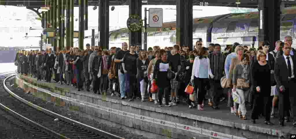 Commuters arrive at the Saint Lazare station in Paris with one of the few trains available.  French rail workers are on strike to protest a reorganization of the national rail and train companies.