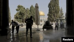 Palestinians clean the Al-Aqsa mosque after clashes between Israeli police and Palestinians on the compound known to Muslims as Noble Sanctuary and to Jews as Temple Mount in Jerusalem's Old City, Sept. 15, 2015.