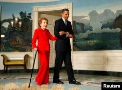 Tổng thống Barack Obama dìu cựu Đệ nhất Phu nhân Nancy Reagan đến dự buổi lễ ký ban hành một đạo luật mang tên chồng bà tại Tòa Bạch Ốc, ngày 2 tháng 6, 2009.