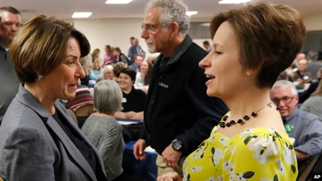Democratic presidential candidate Sen. Amy Klobuchar, center, talks with State Rep. Heather Matson, right, at the Ankeny Area Democrats' Winter Banquet, Feb. 21, 2019, in Des Moines, Iowa.