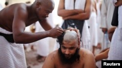 A Muslim pilgrim has his head shaved after casting pebbles at a pillar that symbolizes Satan during the annual hajj pilgrimage, on the first day of Eid al-Adha in Mina, near the holy city of Mecca, Oct. 15, 2013.