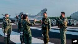 Presiden Taiwan Tsai Ing-wen, tengah, berbicara dengan personel militer di dekat pesawat yang diparkir di jalan raya di Jiadong, Taiwan, Rabu, 15 September 2021. (Kantor Kepresidenan Taiwan via AP)