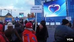 3月18日莫斯科紅場慶祝俄羅斯吞併克里米亞的一個集會上。普京的支持者手舉寫上:我們信任普京的標語牌。 (美國之音白樺)