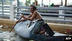 Một người dân ngồi trên một tấm nệm chèo dọc theo sông Chao Pghraya, con sông chảy ngang qua thủ đô Bangkok của Thái Lan