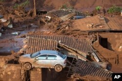 A car and two dogs are seen on the roof of destroyed houses at the small town of Bento Rodrigues after a dam burst on Thursday in Minas Gerais state, Brazil, Nov. 6, 2015.