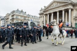 Police secure a zone around a police bus for detained people, at the Place de la Bourse in Brussels, Belgium, April 2, 2016.