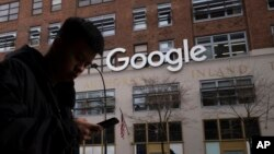 A man using a mobile phone walks past Google offices in New York, Dec. 17, 2018.