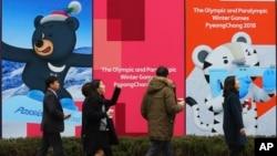지난 17일 서울 거리에 설치된 2018 평창동계올림픽 홍보 포스터 앞으로 시민들이 지나다니고 있다.