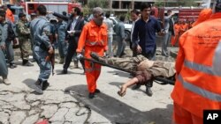 An Afghan municipality worker carries the body of a Taliban after clashes in front of the Parliament, in Kabul, Afghanistan, June 22, 2015.
