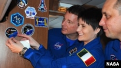 Flight Engineer Samantha Cristoforetti of the European Space Agency (ESA), puts on the ESA logo for her mission. (Photo Courtesy of NASA)