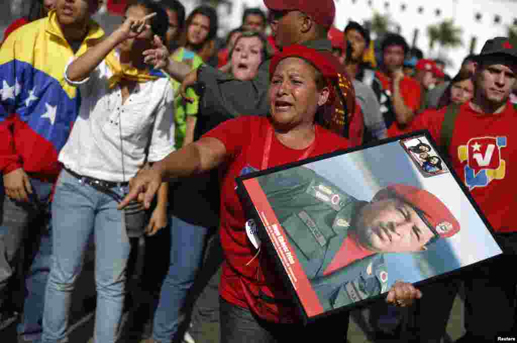 Supporters of Venezuela's late President Hugo Chavez protest over others cutting the line as they wait to view his body in state at the Military Academy in Caracas, March 7, 2013.