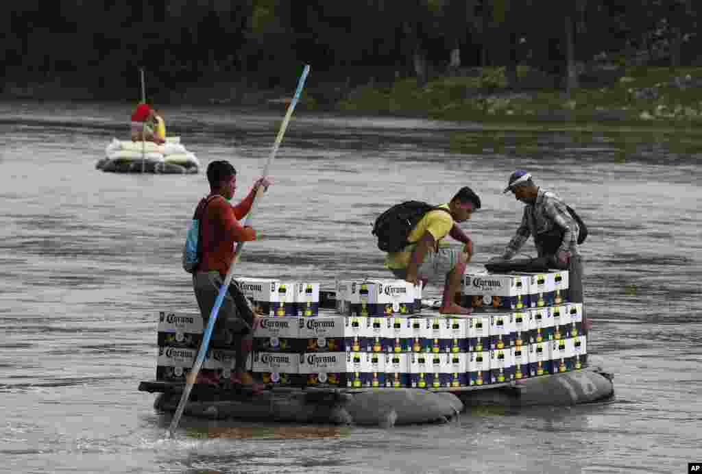 Men cross the Suchiate Rivera with a load of Corona beer on an inner tube and plank raft, near Ciudad Hidalgo, Mexico, June 17, 2019, on the border with Guatemala.