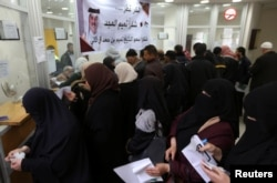 غزہ کے ایک ڈاک خانے میں سرکاری ملازم اپنی تنخواہیں ملنے کا انتظار کر رہے ہیں۔ 7 دسبمر 2018