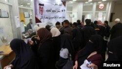 غزہ کے سرکاری ملازم ڈاک خانے میں اپنی تنخواہ وصول کر رہے ہیں۔ تنخواہیں قطر نے عطیہ کی ہیں۔ دیوار پر لگے بینر میں قطر کا شکریہ ادا کیا گیا ہے۔ 7 دسمبر 2018