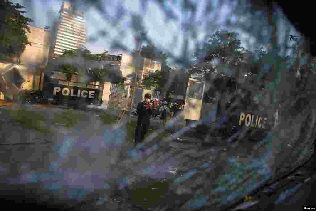 A Thai security officer is seen through a shattered windscreen of a destroyed police truck at the Thai-Japan youth stadium in central Bangkok, Thailand, Dec. 27, 2013.