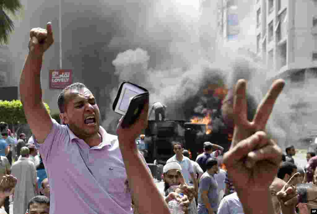 Supporters of Egypt's ousted President Mohammed Morsi chant slogans against Egyptian Defense Minister Gen. Abdel-Fattah el-Sissi during clashes with Egyptian security forces in Cairo's Mohandessin neighborhood, Egypt, Wednesday, Aug. 14, 2013. Egyptian se