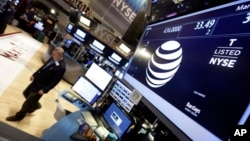 A trader walks by the post that handles AT&T on the floor of the New York Stock Exchange, March 6, 2015.