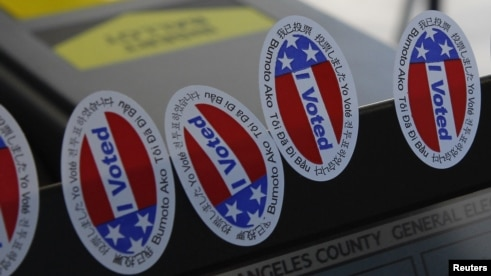 "Stickers stating ""I Voted"" in several languages are affixed to a ballot machine in Los Angeles, California."