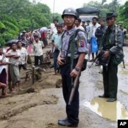 ຕໍາຫລວດແລະທະຫານມຽນມາ ຍາມຮັກສາຄວາມ ສະຫງົບ ໃຫ້ພວກອົບພະຍົບມຸສລິມ ໃກ້ໆຄ້າຍອົບ ພະຍົບ ໃນ Sittwe ເມືອງຫລວງຂອງລັດ Rakhine ໃນພາກຕາເວັນຕົກຂອງມຽນມາ, ວັນທີ 14 ມິຖຸນາ 2012. (AP Photo/Khin Maung Win)