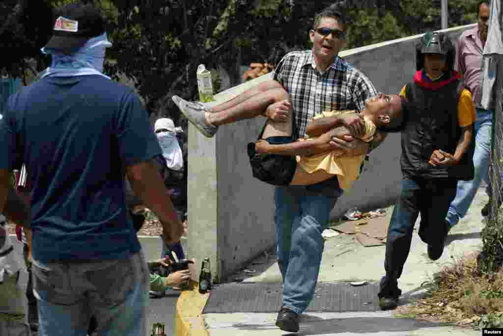 In the city of in San Cristobal, a man carries an injured protester at a demonstration against Venezuelan President Nicolas Maduro's government.