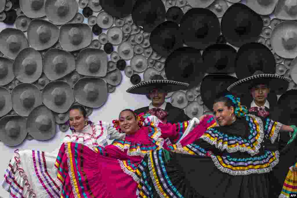 Mexican regional dancers perform in front of a mosaic made with Mexican traditional hats, during a Guinness record ceremony for the world's largest mosaic made with hats, in Guadalajara. The mosaic was made with more than 1,000 hats and measures 10 meters high.