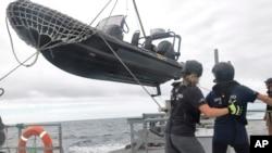 Members of Sea Shepherd, an ocean conservation group, lower an inflatable dinghy from the deck of the Ocean Warrior off the west coast of South America on July 17, 2021.