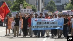 Anti-Japan protesters march to the Japanese Consulate in Hong Kong Sunday, Sept. 26, 2010 as they demand for an apology from Japan for the detention of a Chinese fishing boat captain.