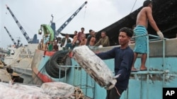 Workers unload frozen fish from a Thai fishing boat in Ambon, Indonesia.