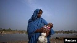 سیلاب سے متاثرہ ایک خاتون اپنے بچے کو گود میں سنبھالے کھڑی ہے۔