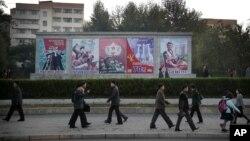 지난해 10월 평양 시민들이 출퇴근 길에 선전 문구 앞을 지나고 있다. (자료사진)