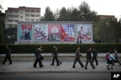 Người dân Bắc Triều Tiên đi bộ ngang qua một áp phích tuyên truyền tại Bình Nhưỡng.