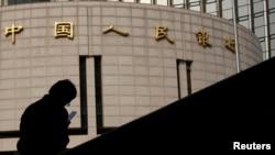 资料照:一名男子坐在中国人民银行总部大楼外。