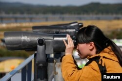 FILE - A Chinese tourist looks towards the north through a pair of binoculars at the Imjingak pavilion near the demilitarized zone which separates the two Koreas.
