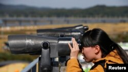 In this file photo, a Chinese tourist looks towards the north through a pair of binoculars at the Imjingak pavilion near the demilitarized zone which separates the two Koreas, in Paju, north of Seoul, Oct. 16, 2013.