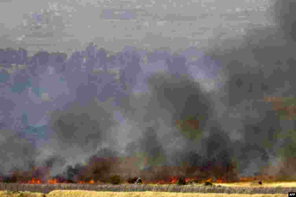 In this picture taken from the Israeli side along the Israel-Syria ceasefire line in the Golan Heights shows smoke billowing from a fire caused by clashes between Syrian rebels and forces loyal to the regime near the Quneitra crossing.