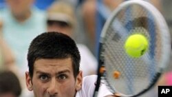 Serbia's Novak Djokovic hits a backhand return against Tomas Berdych, from the Czech Republic, during a semifinal match at the Western & Southern Open tennis tournament in Mason, Ohio, August 20, 2011