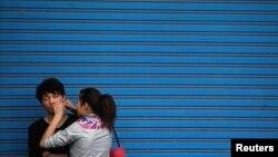 Seorang perempuan sedang membantu pacarnya memencet jerawat di sebuah jalan di Shanghai, 24 April 2012.