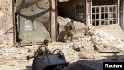 Binh sĩ Syria chạy vào một khu vực bị đổ nát ở al-Arqoub, ngoại ô Aleppo, 23/9/12