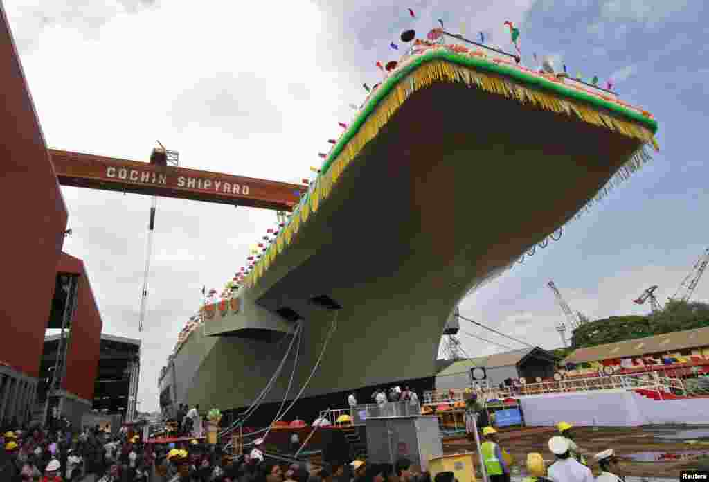 Employees of Cochin Shipyard stand beside India's Indigenous Aircraft Carrier P-71 'Vikrant' built for the Indian Navy during its launch in the southern Indian city of Kochi, India.