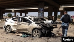 A member of the Iraqi security force inspects the site of a car bomb attack in Ramadi, April 16, 2014.