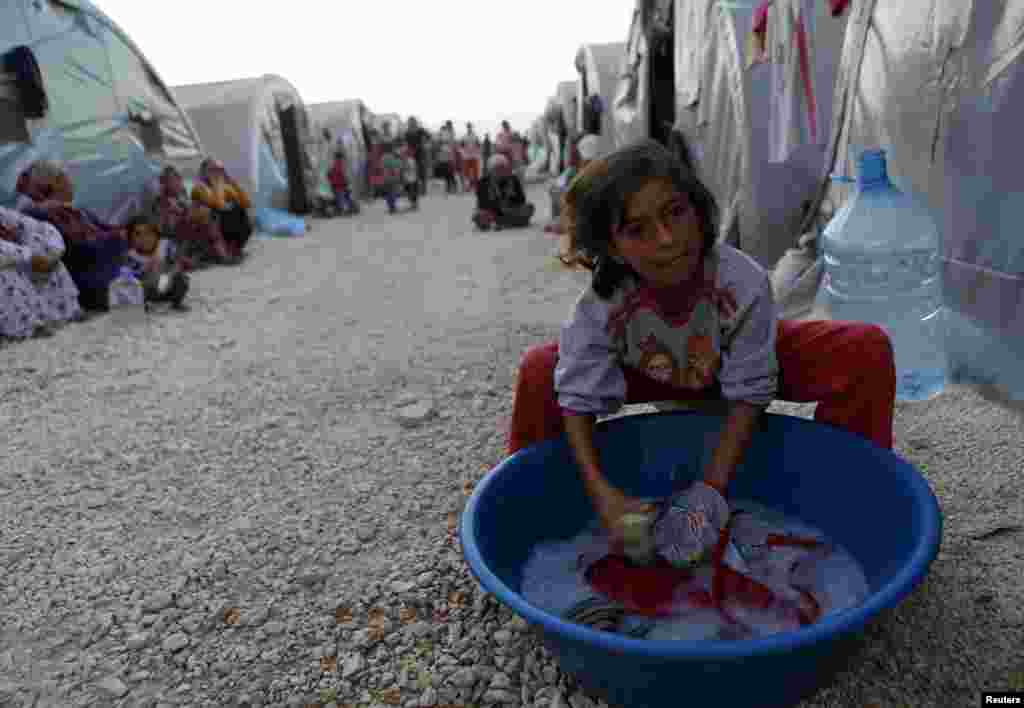 A Kurdish refugee girl from the Syrian town of Kobani washes in front of their family tent in a camp in the southeastern town of Suruc, Sanliurfa province. The U.S. military conducted nine airstrikes against Islamic State militants in Syria during the past two days, including seven strikes near the border town of Kobani.
