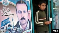 Seorang anak Palestina berdiri di dekat poster komandan Hamas, Mahmoud al-Mabhouh. (foto: dok)