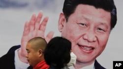 北京街头的习近平大幅照片海报前,有行人走过,有人戴口罩(2017年10月26日)