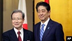 아베 신조 일본 총리(오른쪽)가 29일 도쿄의 중국대사관에서 열린 중국 국경절 및 중일 국교정상화 45주년 기념식에서 청융화 주일 중국대사와 악수하고 있다.