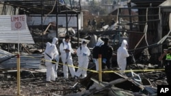Soldiers and investigators walk through the scorched rubble of the open-air San Pablito fireworks market that exploded in Tultepec on the outskirts of Mexico City, Dec. 21, 2016. The market was especially well stocked for the holidays and bustling with hundreds of shoppers when a powerful chain-reaction explosion ripped through its stalls Tuesday, killing and injuring dozens.