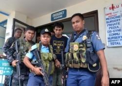 Polisi Filipina bersenjata mengawal warga negara Indonesia, Muhamad Sofyan ketika mereka meninggalkan rumah sakit di kota Jolo, Provinsi Sulu, di selatan pulau Mindanao pada 17 Agustus 2016, setelah dia melarikan diri dari para penculiknya, kelompok Abu Sayyaf. (Foto: AFP)